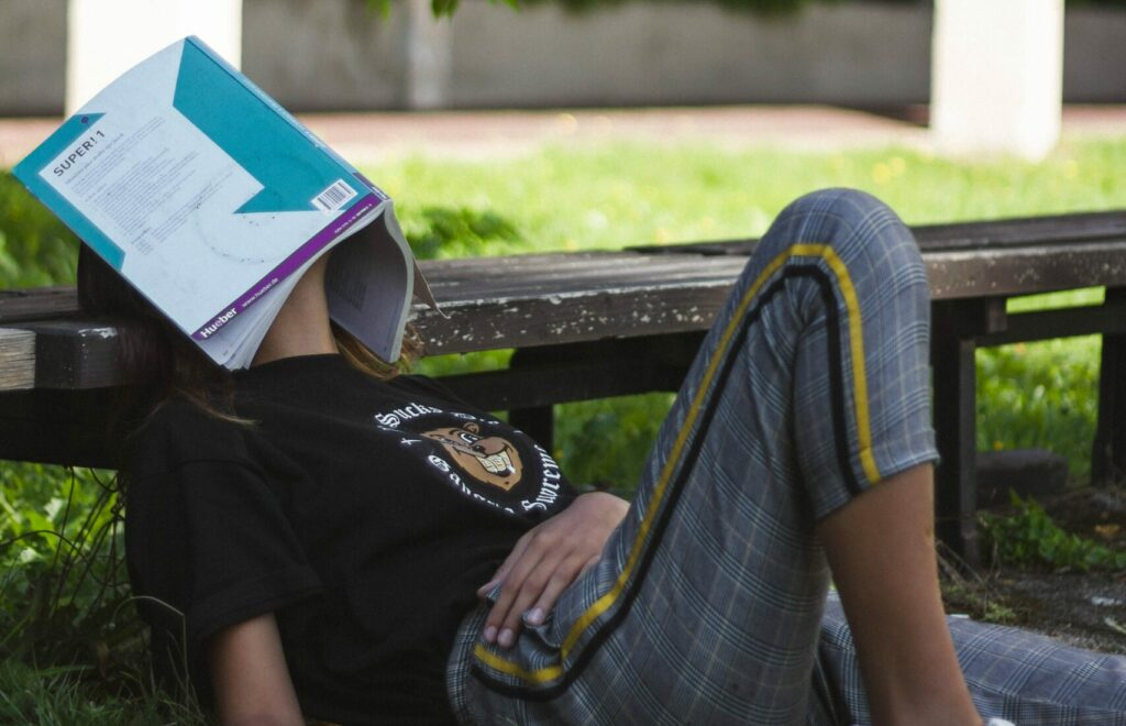 Student sleeping in park with an open textbook on their face